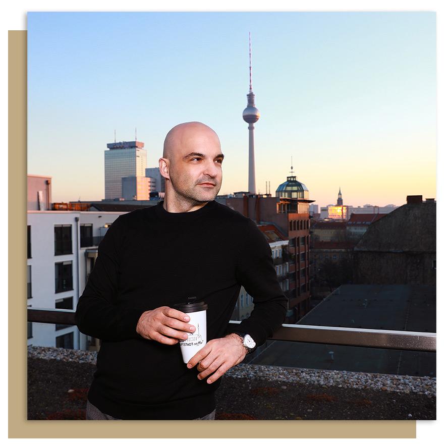 HAUPTSTADTcaffee Mann hält ToGo Becher in der Hand haltend vor der Berliner Skyline