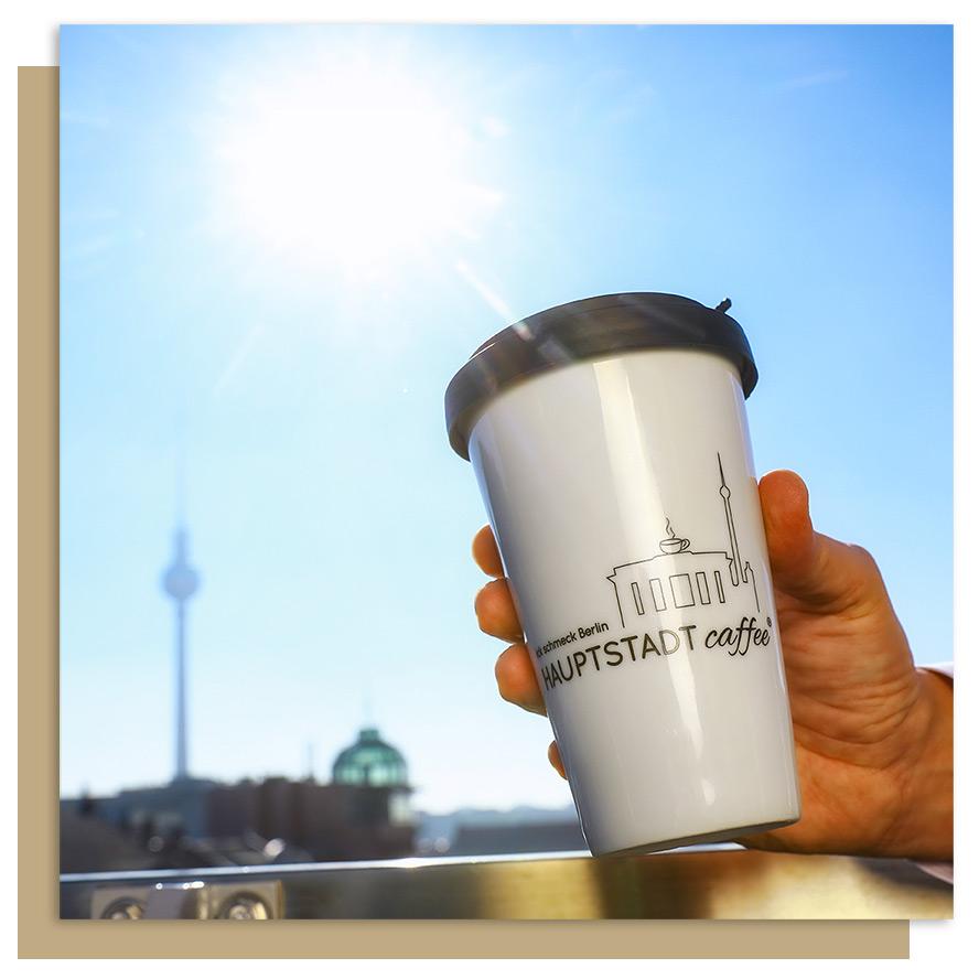 HAUPTSTADTcaffee ToGo Becher in der Hand haltend vor der Berliner Skyline